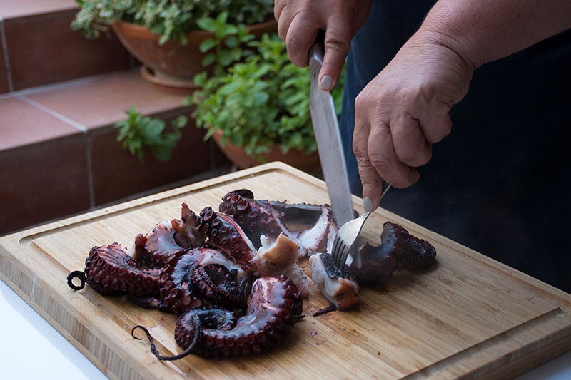 Cutting the cooked octopus Odyssey Poros Greece