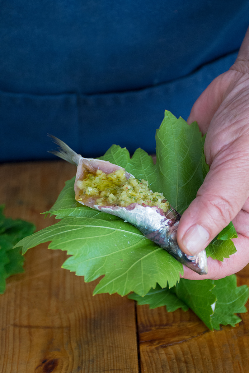Wrapping sardines in grape leaves Odyssey Poros Greece