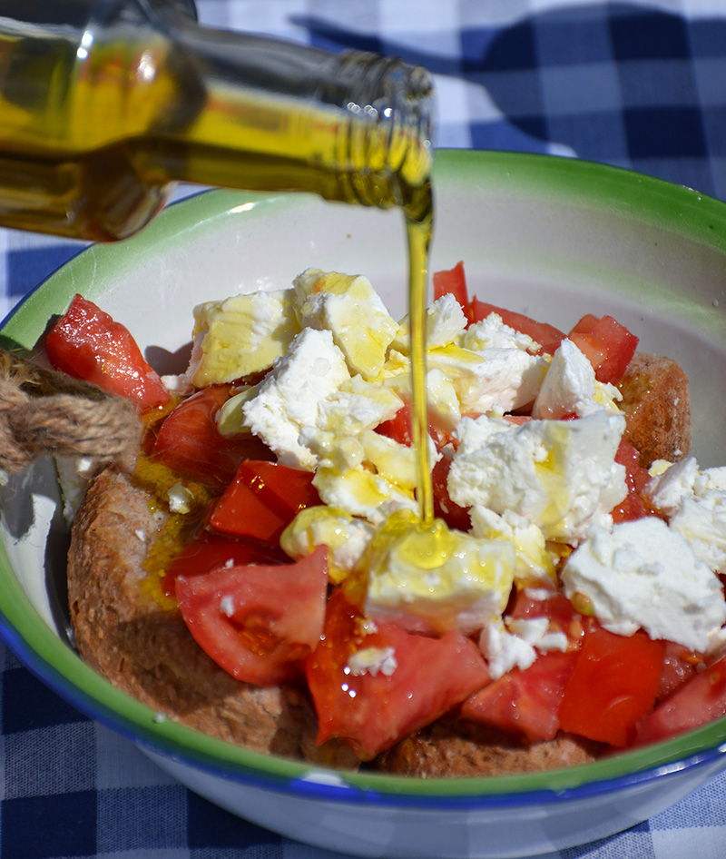 Pouring-olive-oil-over-the-Dakos