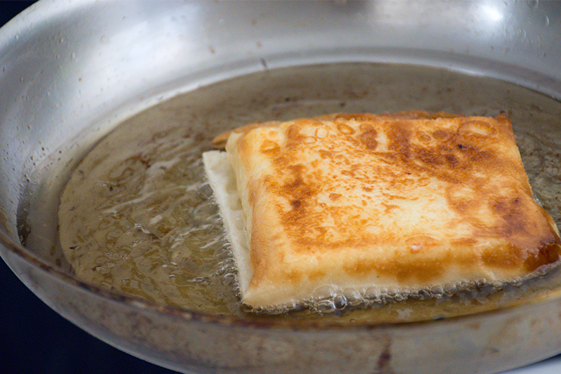 Frying the feta-filo parcels Odyssey Poros Greece